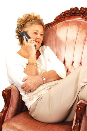 An senior woman sitting in a ping armchair and talking on the phone.  photo
