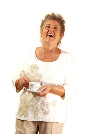 An senior woman with a coffee cup in her hand standing in a studio and having great fun.  photo