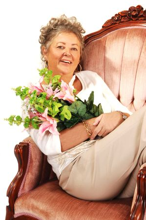 An senior woman sitting in a ping armchair and holding nice flowers. Stock Photo - 4055259