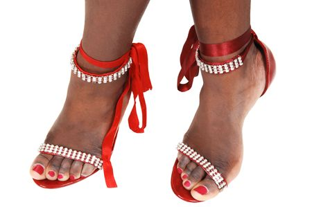 Young womans feet with red and silver fashion sandals and red ripens.  photo