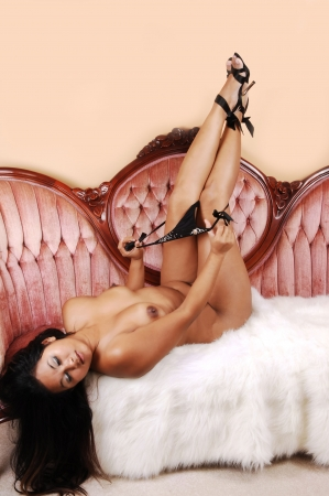 An pretty young Asian woman lying on a pink sofa, topless and taking her black panties of. Her long black hair hangs down to the floor. photo