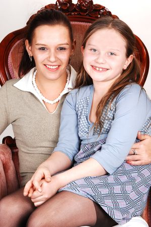 A happy smiling daughter sitting on the lap of her mother in an pink armchair.