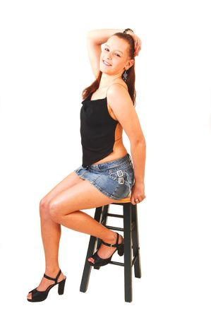 Young pretty woman with red hair on a bar chair posing for the camera. Stock Photo - 4178823
