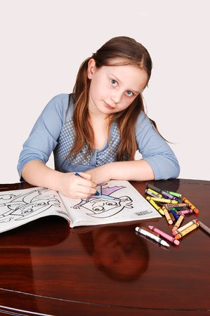 Little girl in a blue sweeter sitting on the table and coloring an book with crayons. Her face mirroring in the table. Stock Photo - 4205365