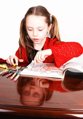 Little girl in a red sweeter sitting on the table and coloring an book with crayons. Her face mirroring in the table. Stock Photo - 4205370