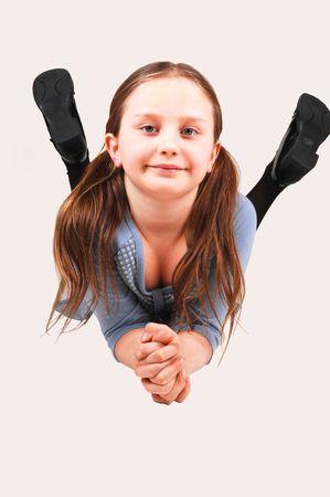 な少女、スタジオの床に彼女の胃に横たわると、カメラに笑顔します。 写真素材