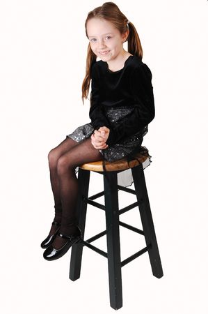 An little girl sitting on a high chair and looking in the camera waiting. what it is happening now.