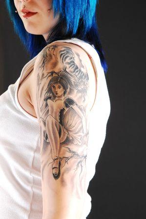 sexy tattoo: Niza tatuaje en el brazo de una chica linda en una camiseta blanca y pelo azul brillante sobre fondo negro.