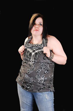 Una giovane ragazza poco pesanti in jeans e top grigio in piedi in studio per sfondo nero. Archivio Fotografico - 4359949