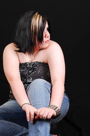 A young little heavy girl in jeans and gray top sitting in the studio for black background. Stock Photo