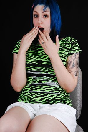 A young girl with blue dyed hair sitting on an chair in green top and white shorts is very scared of what she is seeing. photo