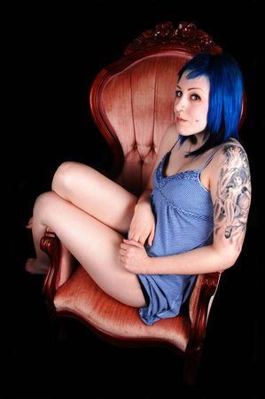 A beautiful blue dyed hair girl, sitting in an pink armchair with a nice  tattoo on her arm in a short dress for black background.