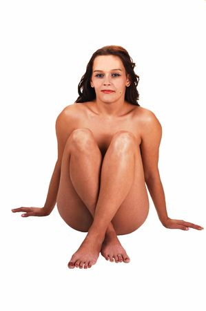 pretty young girl sitting naked on the floor in a studio and smiling in the camera, on white background. photo