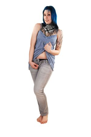 Young blue dyed hair girl is posing for the camera in gray jeans and an short light blue dress with a nice tattoo on her arm for white background. photo