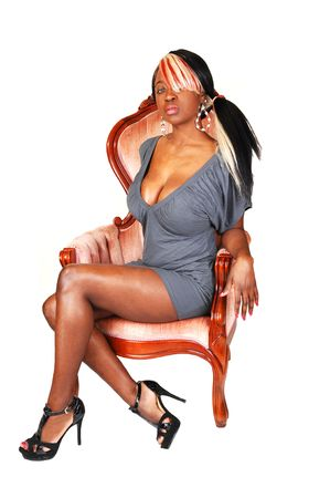 A beautiful jamaican woman with long colored hair, sitting in an pink armchair  with a nice gray dress and long legs. photo