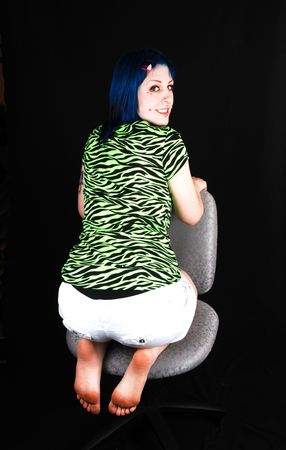 A beautiful blue dyed hair girl, kneeling backwards on an office chair in the green and black top and white shorts for black background. photo