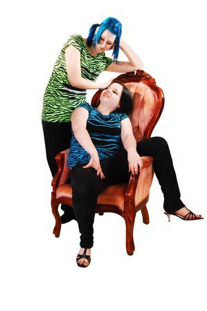 Two girlfriends, one sitting in a pink armchair and her friend standing behind with nice blue hair on white background. photo