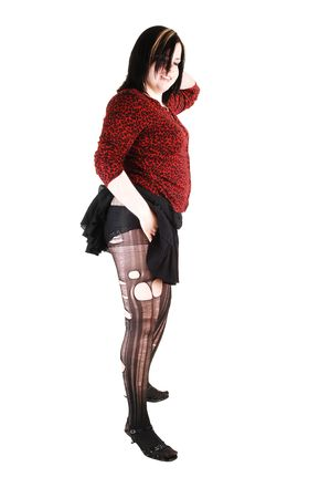 Young woman standing in the studio with a red blouse and black short skirt shooing her panties and the ripped pantyhose. photo