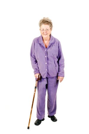 Senior woman with gray hair and an lilac suit needs the help of a cane to get around. On white background.