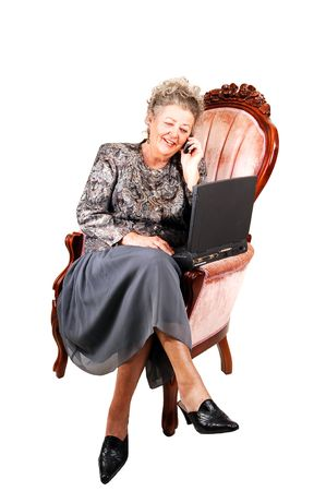 Busy businesswoman talking on the cell phone and working also on the laptop, sitting in a pink armchair, over white background. Stock Photo - 4556446