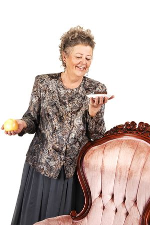 An elderly woman has to make a choise between an healthy apple on a sweet and delicious piece of shocolate cake. Over white background. photo