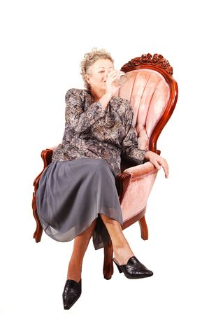 All dressed up elderly woman sitting in an pink armchair, enjoying her life and having a glass of water, for white background.. Stock Photo