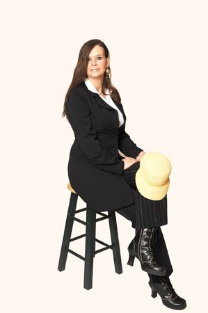 Middle age woman in an black coat and boots sitting on a bar chair in the studio for light beige background, Stock Photo - 4796439