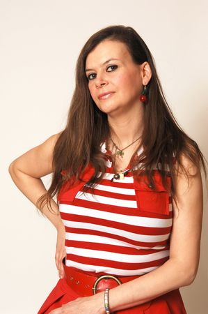 Pretty woman with long brown hair sitting on a chair for a portrait in an red dress for light beige background and looking in the camera. Stock Photo - 4796446
