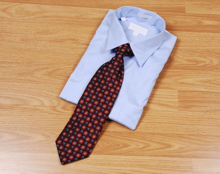 A light blue dress shirt on a wood surface with an red and black tie for sale in the store.