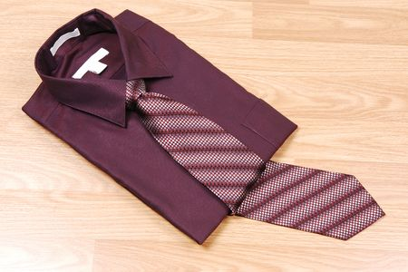 Burgundy dress shirt on a wood surface with an burgundy and beige tie for sale in the store. photo
