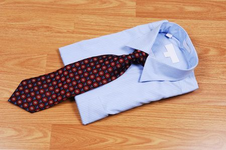 A light blue dress shirt on a wood surface with an red and black tie for sale in the store. photo