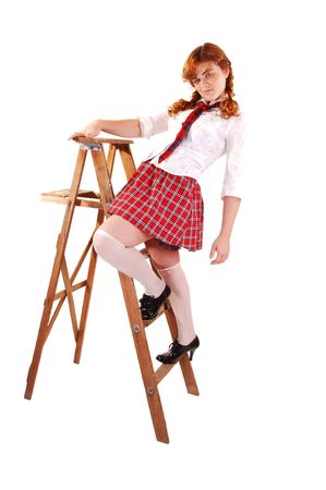 A young red haired schoolgirl in her uniform standing on an stepladder  and playing around.