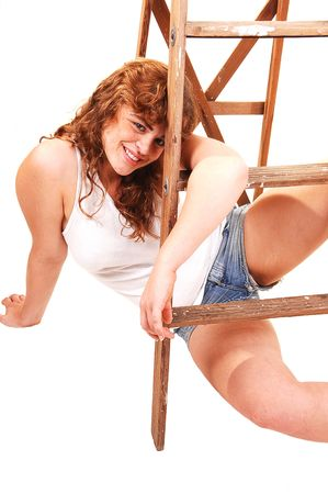 Young red haired girl in short shorts and t-shirt playing with a stepladder. Stock Photo - 4831459