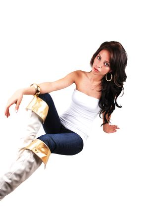 A slim pretty girl in an white top, blue jeans and with boots with gold border and long black hair sitting on the floor in the studio.