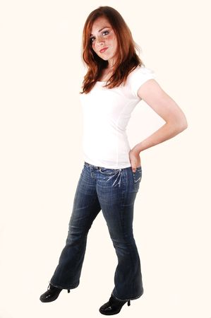 Tall lovely teenager in a white top and jeans with high heels standing in an studio shooing her bright red hair. Stock Photo - 4931451