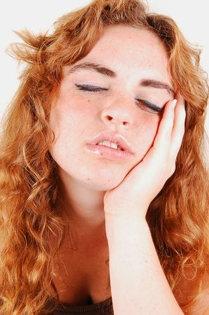 An young bright red haired girl is very tired and sleeps when she is standing. Stock Photo
