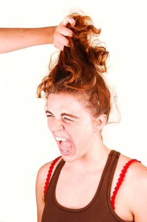 Young woman is screaming when another girl is pulling her red hair up. Stok Fotoğraf