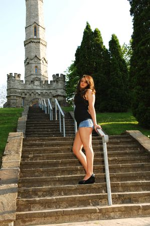 An pretty young girl standing on the stairs to a tall monument in an nice park, in short jeans shorts with nice legs.