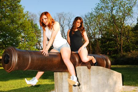 Two red haired sisters in short jeans shorts sitting on a bronze cannon in the park and having fun.
