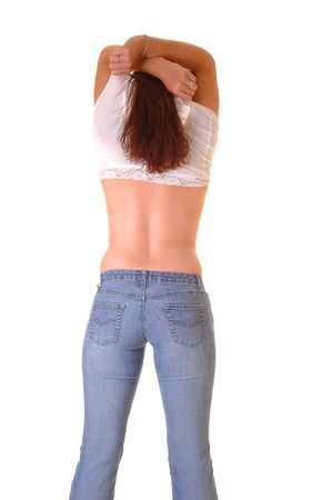 Young pretty girl taking her white shirt off and the long brown hair shooing. Standing with the back to the camera in jeans.