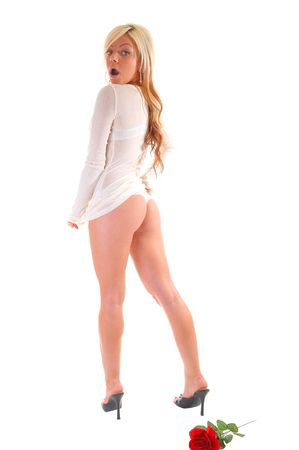 A lovely young girl in an white sweater and thong, shooing her nice butt is surprised that somebody is seeing her so. Stock Photo