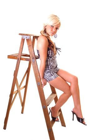 Pretty young girl in a black and white top and shorts with long blond hair sitting on the wooden stepladder, looking in the camera.