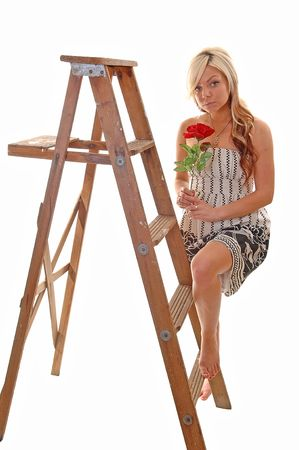 Pretty young girl in a black and white dress with long blond hair standing on the wooden stepladder, looking in the camera. photo