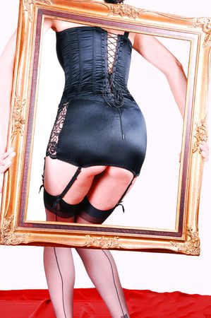Pretty tall girl standing in lingerie on red silk, holding an old picture frame in her hand and shooing her butt trough the frame. photo