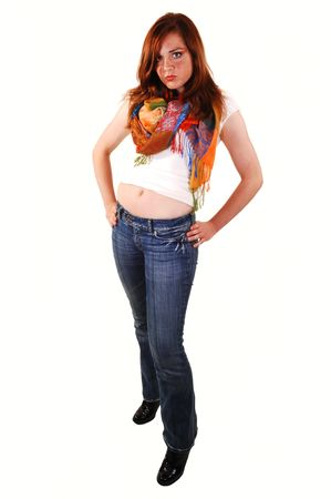 Red haired teenager in jeans and white top with a colorful scarf, shooing  her belly button, standing in the studio for white background.
