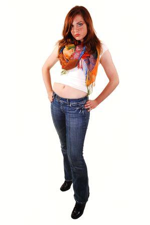 Red haired tiener in jeans en witte bovenzijde met een kleurrijke sjaal, shooing haar navel, staande in de studio voor witte achtergrond.