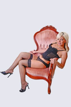 Beautiful blond young girl sitting in a pink armchair in black lingerie and fishnet stockings on her nice legs, looking in the camera.