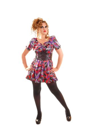 Beautiful red haired woman in a colorful dress with a big belt, black pantyhose and high heels standing in the studio wit her hands on the hips. photo