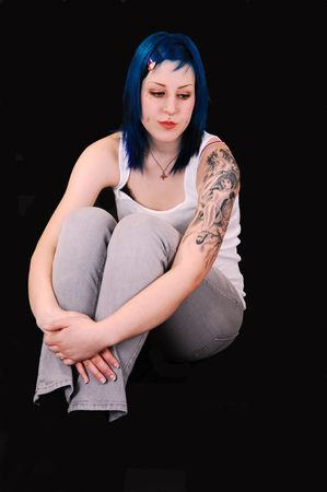 A very sad looking young girl with blue hair and a big tattoo on her lefty arm, sitting on the floor for black background, and the arms grossed around  the legs. photo
