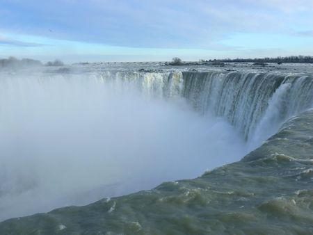 the edge of horseshoe falls: The horseshoe falls in niagara falls Canada on a winter day with mist coming up, a close-up.